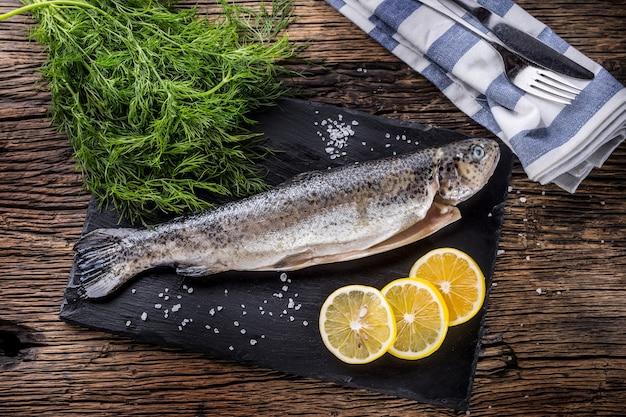 素朴なオークのテーブルにハーブディルレモンと塩を添えた生の魚のマス。