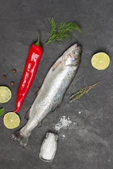 生の魚のマスとレモンのくさびと唐辛子。黒の背景。フラットレイ。