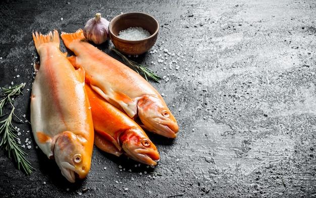 로즈마리, 마늘, 소금 검은 나무 테이블에 생선 송어