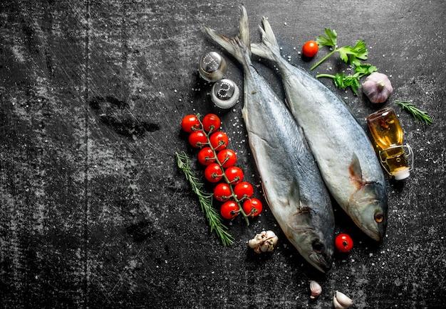 어두운 시골 풍 테이블에 로즈마리, 파슬리, 향신료와 마늘을 곁들인 생선 참치