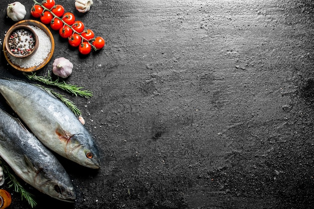 토마토와 생선 참치. 로즈마리와 마늘. 검은 소박한 배경에