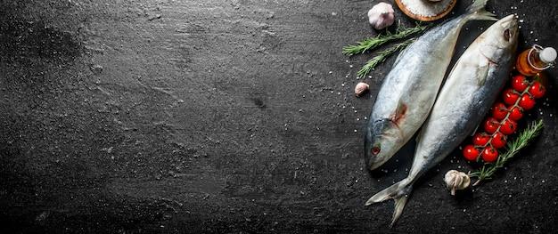 토마토와 생선 참치. 로즈마리와 마늘 검은 시골 풍 테이블