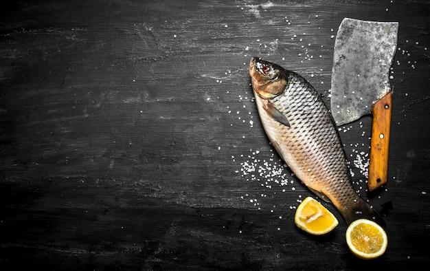 黒い木製のテーブルに斧を持つ生の魚。