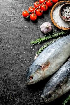체리 토마토와 향신료와 생선. 검은 소박한 배경에