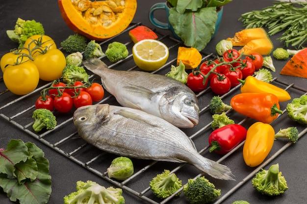 グリルの火格子に色とりどりの野菜と生の魚。