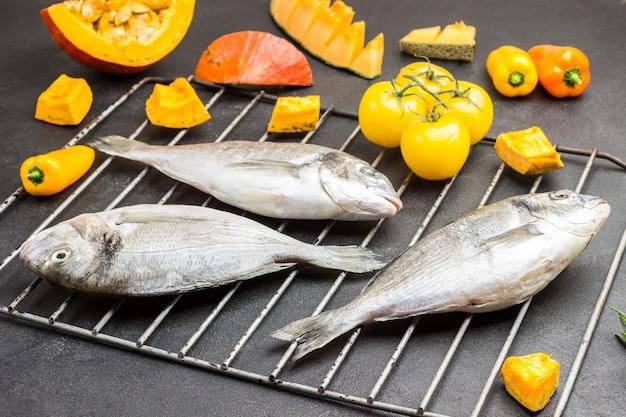 グリル火格子に色とりどりの野菜と生の魚