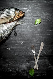 Raw fish with cutlery and laurel leaves on black wooden table.
