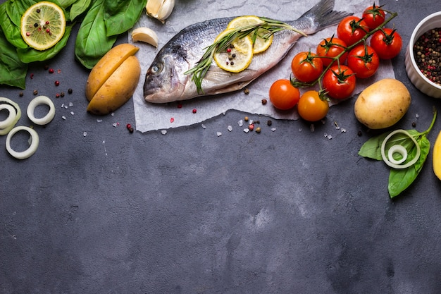 Raw fish with fresh ingredients ready to cook. fish, lemon, herbs, potato, tomatoes. ingredients for cooking on dark rustic background.