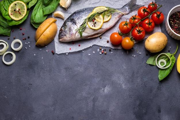 Сырая рыба со свежими ингредиентами, готовая к приготовлению. рыба, лимон, зелень, картофель, помидоры. ингредиенты для приготовления на темном деревенском фоне.