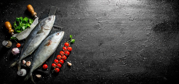 Raw fish with knife, tomatoes and parsley on black rustic table