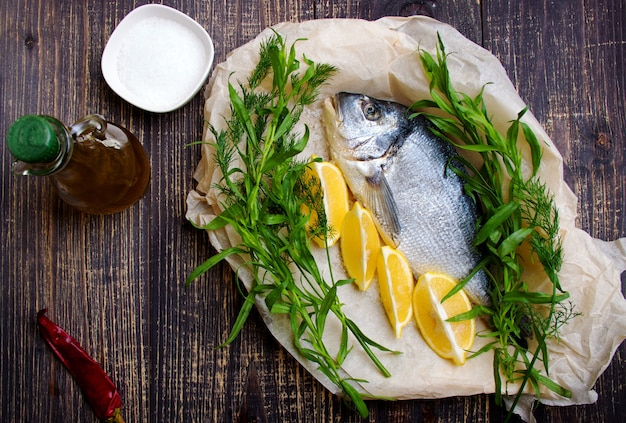 Raw fish with lemon and aromatic herbs, pepper and olive oil prepared for baking.
