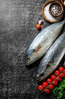 어두운 시골 풍 테이블에 파슬리, 체리 토마토, 향신료와 생선