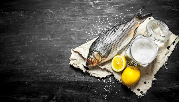 塩とレモンの生魚。黒い木製の背景に。