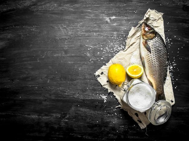黒い木製のテーブルに塩とレモンと生の魚。