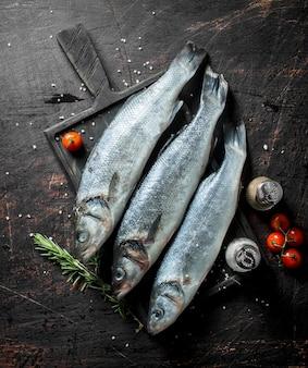 暗い素朴なテーブルにスパイスとチェリートマトと生の魚