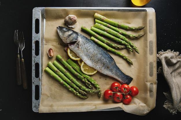 Сырая рыба со специями и овощами спаржа на противне готова к приготовлению
