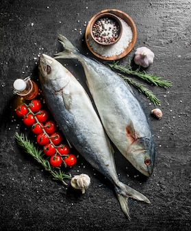 Raw fish with spices, rosemary and garlic cloves on black rustic table