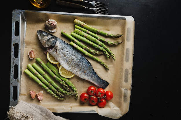 Raw fish with spices and vegetables asparagarus on baking sheet ready to be cooked