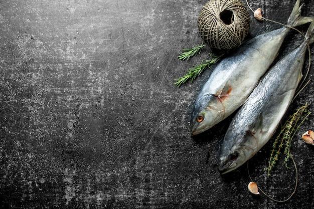 백리향, 로즈마리, 어두운 시골 풍 테이블에 오래 된 꼬기와 생선
