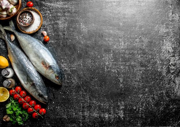 Сырая рыба с помидорами, специями и лимоном на темном деревенском столе
