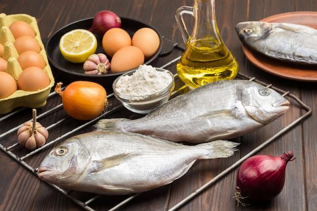 グリルの火格子に野菜と生の魚。