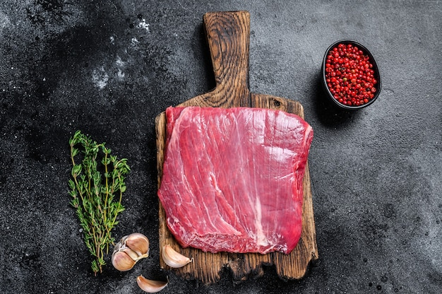 Raw flank or flap beef meat steak on a wooden cutting board