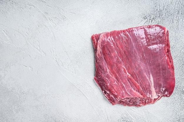 원시 측면 또는 플랩 쇠고기 고기 스테이크. 흰 바탕. 평면도. 공간을 복사합니다.