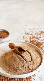 Raw flax seeds flour in a ceramic plate with a spoon close up