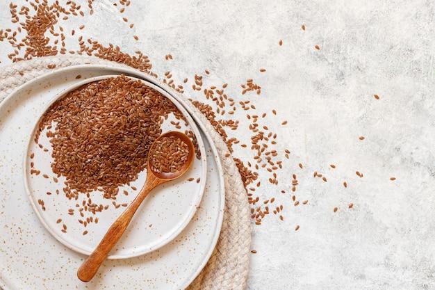 Мука из сырых семян льна в керамической тарелке с ложкой сверху