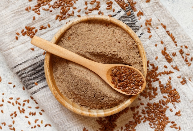Raw flax seeds flour in a wooden bowl with a spoon top view