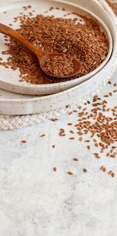 Сырые семена льна в керамической тарелке с ложкой крупным планом