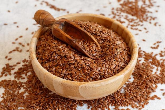 Сырые семена льна в деревянной миске с ложкой