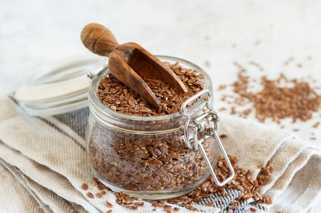 Raw flax seeds in a jar with a scoop close up