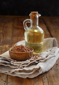 Raw flax seeds and oil on a wooden table close up