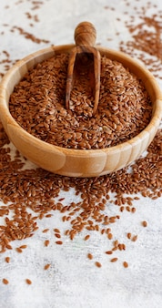 Raw flax seeds in a wooden bowl close up