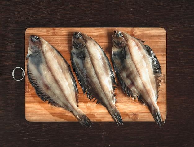 生のヒラメの魚、木製のまな板のシーフード。健康的な食事の概念。上面図