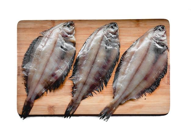 白い背景で隔離の木製まな板に生のヒラメ魚シーフード健康的な食事