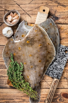 Raw flounder flatfish on butcher board with cleaver. wooden background. top view.