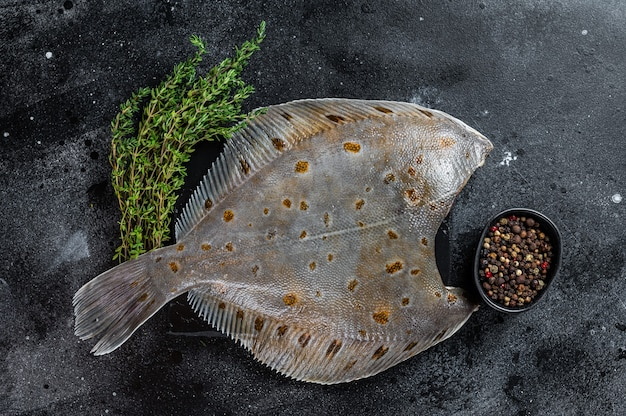 Raw flounder flatfish fish on marble board with thyme. black background. top view.