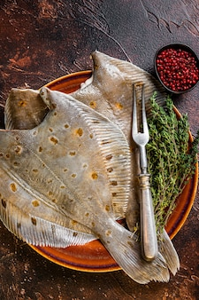 Raw flounder or plaice on rustic plate with herbs. dark background. top view.