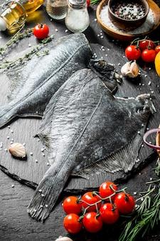 ミニトマト、スパイス、ニンニクのクローブを添えた生のヒラメ。暗い素朴な背景に