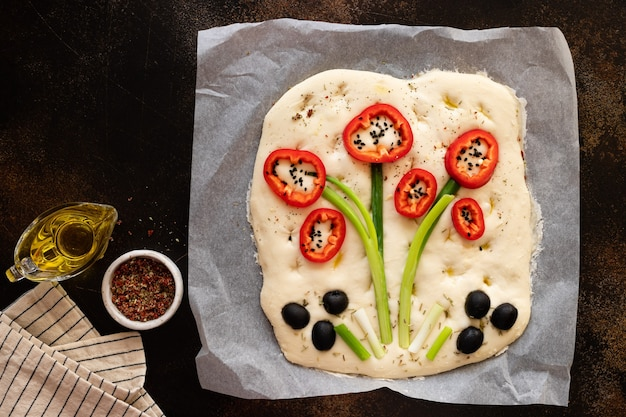 Сырая фокачча, украшенная овощами и зеленью, на темном столе итальянская фокачча