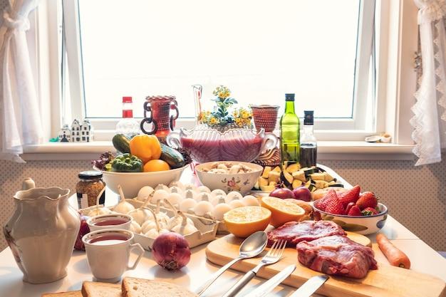 Сырая говядина, яйцо с овощами здоровой пищи, фрукты, приготовленные на столе на ужин