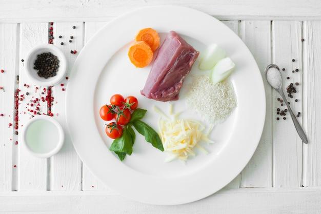 白い木の板の表面に立っている白い皿に豚肉とご飯を調理するための生の食品