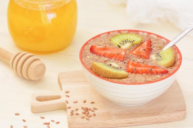 Raw food, vegan breakfast. flaxseed porridge with honey, strawberries and kiwi.