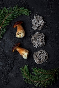 Тальятелле сырые лесные грибы на темном