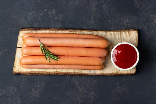 Сырые сосиски с кетчупом на разделочной доске. вид сверху.
