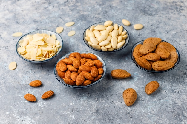 Raw fresh almonds with shell, without shelll, almond slices, top view