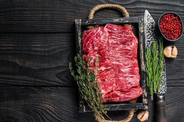 원시 신선한 쇠고기 양지머리는 나무 쟁반에 허브와 함께 고기를 잘라냅니다. 검은 나무 배경. 평면도. 공간을 복사합니다.