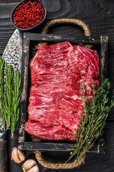 Сырая свежая говяжья грудинка нарезать мясо с зеленью на деревянном подносе. черный деревянный фон. вид сверху.